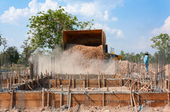 Drehen Sie Lader Bagger, der Sand während des Hausbaus entlädt Stockbild