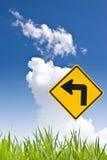 Drehen Sie linkes Zeichen mit Gras und nettem Himmel Stockfotos