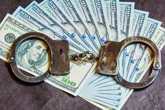 Drehen Sie sich von Rechnungen amerikansih Dollar und Handschellen Stockfoto