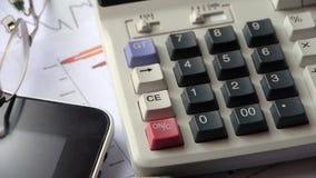 Drehen von Taschenrechner- u. Tabletten-PC mit Geschäftsdiagrammdiagramm auf Tabelle stock video