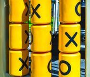 Drehende gelbe Zylinder mit einem Spiel der Tic-TACzehe für Kinderunterhaltung lizenzfreies stockfoto