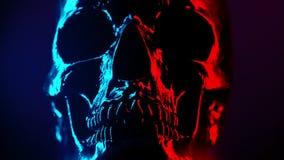 Drehende Nahaufnahme des alten menschlichen Schädelkopfes Neontürkis und rotes Licht Gespenstisch und unheimlich Zauber, Disco, H stock footage