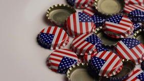 Drehender Schuss von Flaschenkapseln mit der amerikanischen Flagge gedruckt auf ihnen stock footage