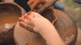 Drehendes Töpfer ` s drehen sich und Lehmwaren auf ihm genommen von oben Ein Kind sculpts seine Hände mit einer Lehmschale auf ei stock video footage