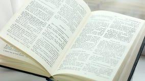 Drehenseiten der heiligen Bibel, Wind, der Seiten des alten Buches, Abschluss herauf das BibelBlättern in Wind leicht schlägt stock footage