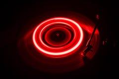 Drehscheibe, die Vinyl mit glühenden abstrakten Linien Konzept auf dunklem Hintergrund spielt Stockfotografie