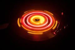 Drehscheibe, die Vinyl mit glühenden abstrakten Linien Konzept auf dunklem Hintergrund spielt Lizenzfreie Stockbilder