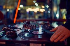 Drehscheibe, Hand von DJ auf der Vinylaufzeichnung am Nachtklub blured Hintergrund lizenzfreie stockfotos