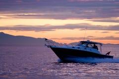Drehzahlboot auf violettem Sonnenuntergang Stockbild