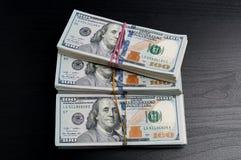 Dreißig tausend Dollar in den Sätzen auf einer Tabelle des dunklen Holzes Lizenzfreies Stockbild