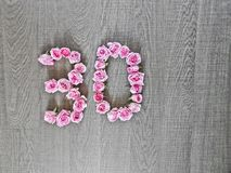 30, dreißig - Weinlesezahl von rosa Rosen auf dem Hintergrund des dunklen Holzes lizenzfreie stockfotos