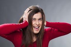 dreißiger Jahre Mädchen, das, leiden unter der Migräne wütend wird und bedecken ihre Ohren mit ihren Händen Lizenzfreie Stockfotos