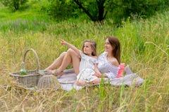 Dreißigjährige schöne junge Mutter und ihre kleine Tochter im weißen Kleid, das Spaß in einem Picknick hat Sie sitzen auf einem P stockfotografie
