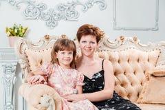Dreißigjährige Frau umarmt ein sechsjähriges Mädchen, das auf einer schönen Couch sitzt und betrachtet die Kamera lizenzfreies stockfoto