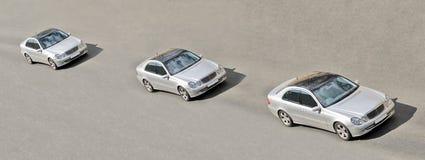 Drei ähnliche Zwillingautos treiben in eine Zeile an Stockbild