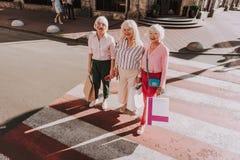 Drei ältere Damen stehen auf Fußgängerübergang stockfoto