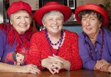 Drei ältere Frauen, die rote Hüte tragen Stockfotografie