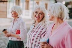 Drei ältere Freundinnen gehen in die Stadt lizenzfreie stockfotos