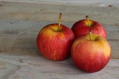 Drei Äpfel auf einem hölzernen Hintergrund lizenzfreie stockfotos