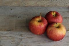 Drei Äpfel auf einem hölzernen Hintergrund stockfotos