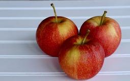 Drei Äpfel auf einem hölzernen Hintergrund stockfoto