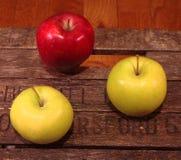 Drei Äpfel auf einem Weinlesekasten Lizenzfreie Stockbilder