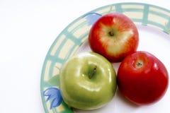 Drei Äpfel auf einer Platte Lizenzfreie Stockfotos