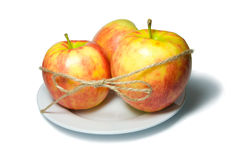 Drei Äpfel auf einer Platte gebunden mit Schnur Stockfotografie