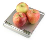 Drei Äpfel auf Kücheskala Lizenzfreie Stockfotografie