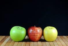 Drei Äpfel mit Apfel in der Backsteinmauerbeschaffenheit Auf Teakholzmattierung und schwarzem Hintergrund Kopieren Sie Platz Stockfoto