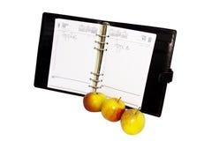 Drei Äpfel mit einem offenen Tagebuch Lizenzfreies Stockbild