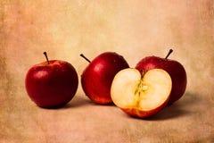 Drei Äpfel und eine Hälfte Stockbilder