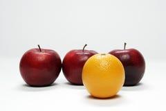 Drei Äpfel und eine Orange Lizenzfreie Stockfotos