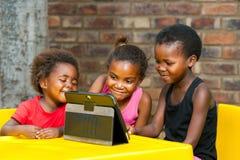 Drei afrikanische Kinder, die zusammen auf Tablette spielen. lizenzfreies stockbild