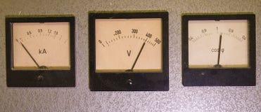 Drei alte analoge Instrumente - Energiefaktormeter, Voltmeter und Amperemeter lokalisiert auf grauem Hintergrund stockfoto