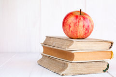 Drei alte Bücher mit rotem Apfel Lizenzfreie Stockfotografie