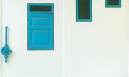 Drei alte Fenster mit grünem Wasserventil auf weißer Wand Stockfoto