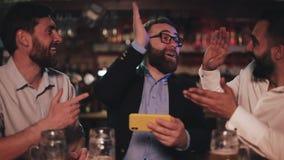 Drei alte Freunde, die Video auf Smartphone aufpassen und Fassbier in der Sportbar trinken Lachende Freunde und sich besprechen