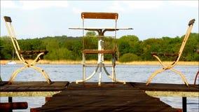Drei alte Stühle und eine Tabelle auf Anlegestelle stock footage