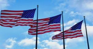 Drei amerikanische Flaggen, die gegen hellblauen Himmel flattern stock video