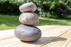 Drei angehäufte Steine auf Kiefernholzoberfläche stockfotos