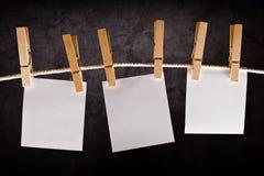 Drei Anmerkungen des leeren Papiers, die am Seil mit Kleidungsstiften hängen Stockbilder