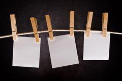 Drei Anmerkungen des leeren Papiers, die am Seil mit Kleidungsstiften hängen Lizenzfreie Stockfotografie