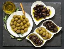 Drei Arten vorgewählte Oliven und Olivenöl Lizenzfreie Stockfotografie