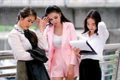 Drei asiatische Mädchen des Geschäfts dienen und ernsthaft über ihre Arbeit während der Tageszeit außerhalb des Büros als unglück stockfoto