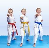 Drei Athleten im karategi schlagen Durchschlagsarm lizenzfreies stockbild