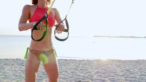 Drei athletisch, sexy junge Frauen in den Badeanzügen, die Lehrer, tuend trainiert mit Eignung trx System, TRX-Suspendierung stock footage