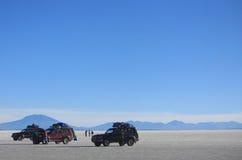 Drei Autos mit Leuten in Salar de Uyuni Lizenzfreies Stockbild