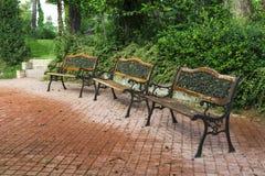 Drei Bänke in einem Park Stockfotos