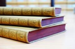 Drei Bücher auf dem Tisch mit einem Bibliothekskatalog im Hintergrund stockfoto